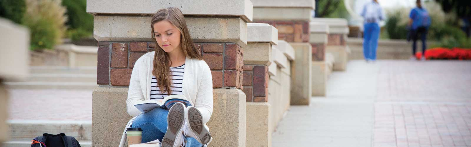 Creighton student reading a book on campus