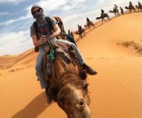 student riding a camel on Morocco